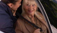 Femme Age d'Or installant une personne âgée dans sa voiture