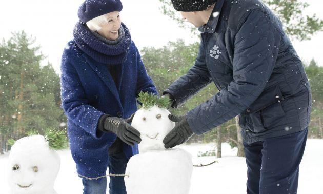 Homme Age d'Or et femme âgée faisant un bonhomme de neige